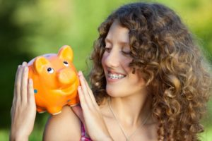Woman with braces in Grafton holding piggy bank