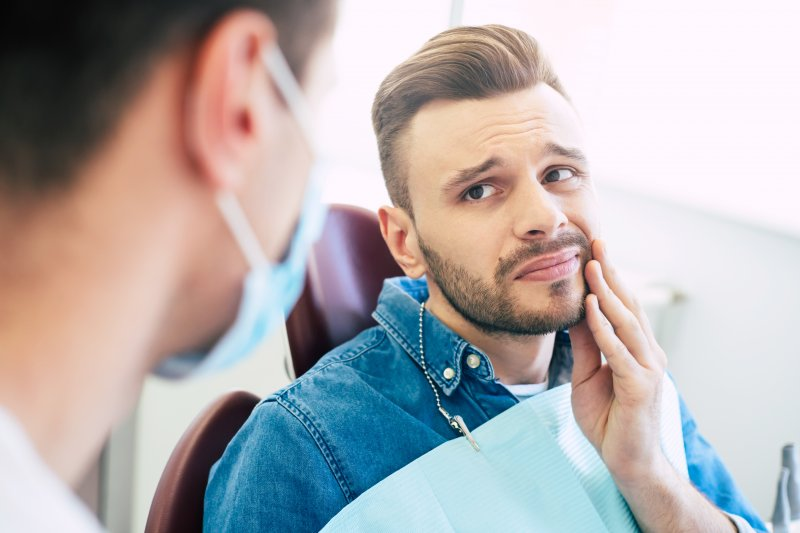 Man speaking to orthodontist about tooth pain