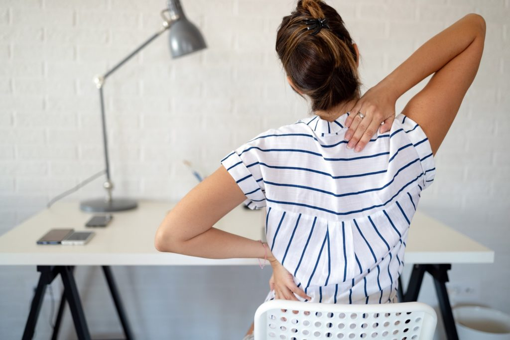 Woman experiencing back soreness after slouching at desk